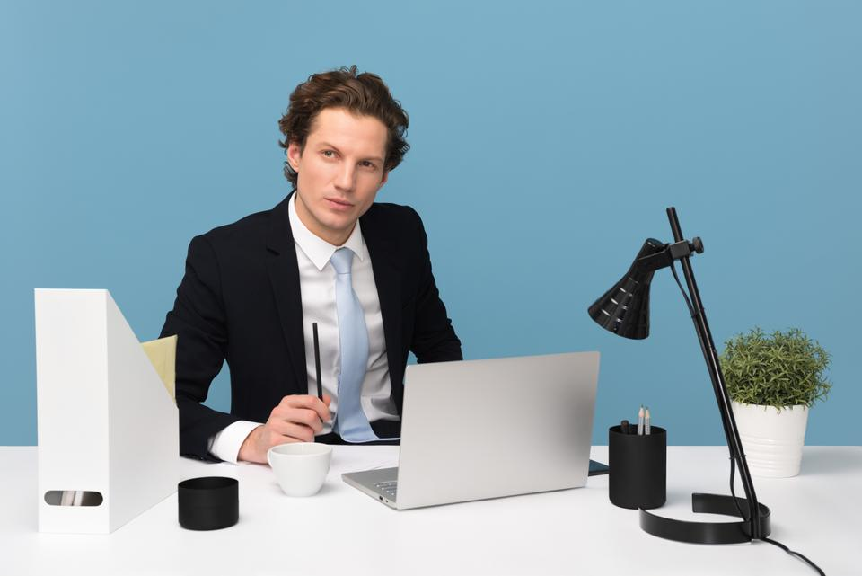 man sitting on chair beside laptop computer and teacup