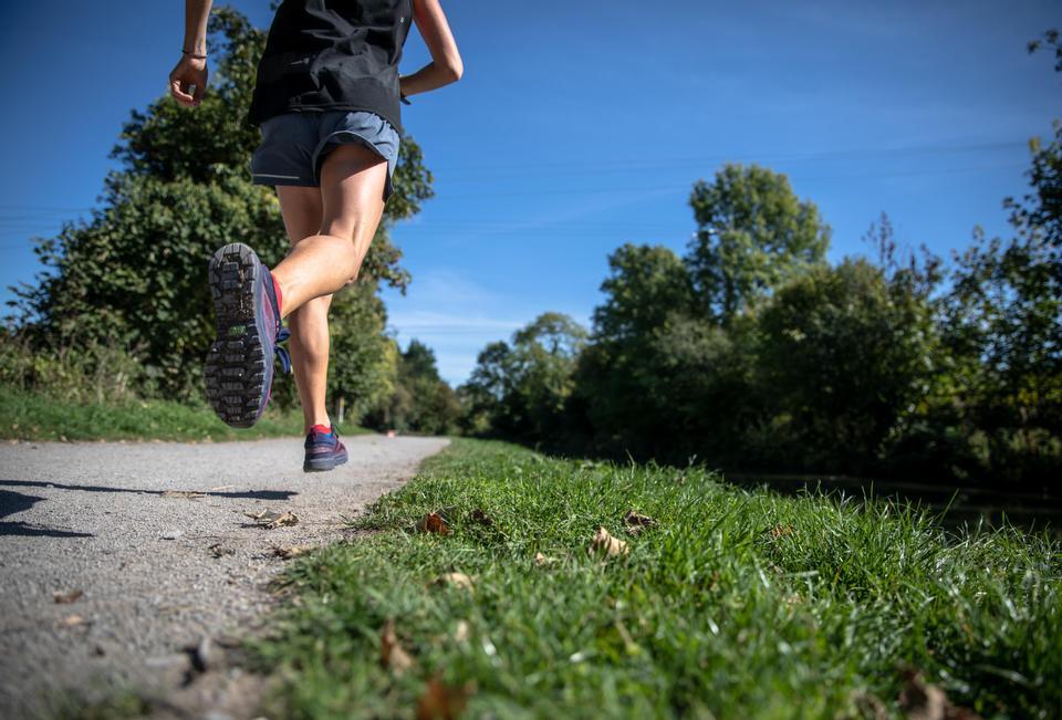 person running between grass fields